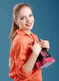 Girl in an orange shirt and jeans with shopping bag on a blue ba Stock Photos