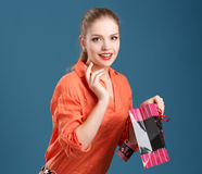 Girl in an orange shirt and jeans with shopping bag on a blue ba. Ckground Stock Photos