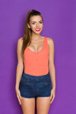 Girl In Orange Shirt Posing At Attention. Cheerful young woman in orange shirt and jeans shorts posing at attention and looking at camera. Three quarter length Stock Photos