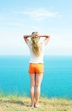 Girl in orange shorts. Is back to his hands behind his head against the blue of the sea Royalty Free Stock Photos