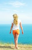 Girl in orange shorts. Is backwards against the blue of the sea Stock Photography
