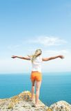 Girl in orange shorts. Standing on a stone arms outstretched against a background of blue sea Stock Photos