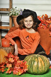 Girl in an orange sweater and hat in Halloween witch. With pumpkins and orange maple leaves Stock Photos