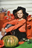 Girl in an orange sweater and hat in Halloween witch. With pumpkins and orange maple leaves Royalty Free Stock Photography
