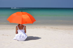 Girl with an orange umbrella royalty free stock photos