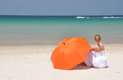 Girl with an umbrella on the sandy beach Royalty Free Stock Photography