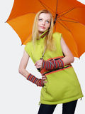 Girl with orange umbrella in a warm jacket. Stock Photos