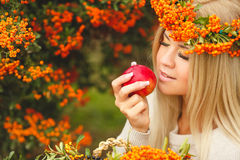 Girl in Orange wreath with Red Apple in hand Stock Photo