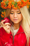 Girl in Orange wreath with Red Apple in hand Stock Image