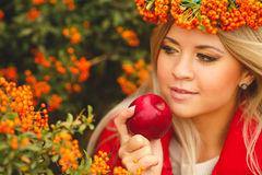 Girl in Orange wreath with Red Apple in hand Royalty Free Stock Image