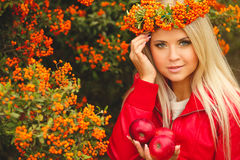 Girl in Orange wreath with Red Apple in hand Royalty Free Stock Images
