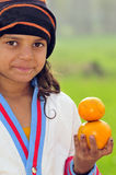 Girl with oranges. Cute girl balancing oranges in her hand Stock Image