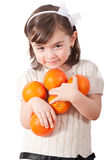 Girl with Oranges. Cute young girl holding several orange fruits isolated on white royalty free stock photos