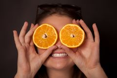 Girl with oranges in the eyes. Is smiling, and sun glasses Stock Images