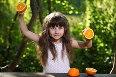 Girl playing with oranges at a table in nature. royalty free stock photos