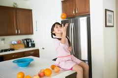 Girl with oranges in kitchen royalty free stock photography