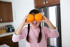 Girl With Oranges in kitchen stock images