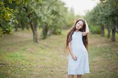 girl in orchard. garden with flowering trees. Allergy season. Dancing jumps stock photo