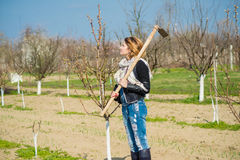 Girl in the orchard. With a hoe on his shoulder Stock Image