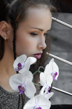 Girl with orchid flower is very sad. Stock Photos