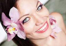 Girl with orchid flowers in hair Royalty Free Stock Photos