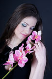 Girl with an orchid. Young beautiful girl holding a branch of orchids Stock Photography