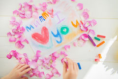 Girl Organising Rose Petals with Drawing for Mummy on the backgr Stock Images
