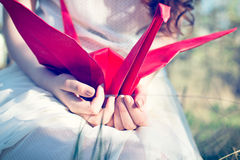 Girl with origami crane. Girl with red origami crane royalty free stock images