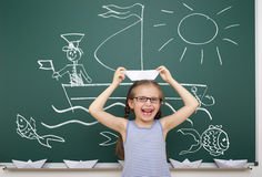 Girl with origami ship drawing on school board Stock Photo