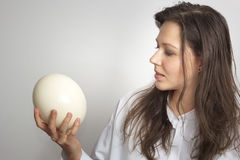 Girl with ostrich egg. In own hand Stock Photos
