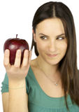 Girl out of focus watching apple in focus Royalty Free Stock Image