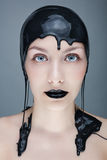 Girl out of the paint. Studio photo of a young woman with black paint on his head Royalty Free Stock Images