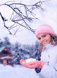 Girl outdoor in winter holds snow in hands Royalty Free Stock Image