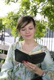 Girl outdoors with Bible Stock Photography