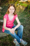 Girl outdoors in the summer sunshine. Twelve year old girl sitting outdoors in the summer sunshine Stock Photography