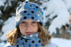 Girl outdoors in a winter hat. Girl wearing a winter hat and scarf outdide in the snow Stock Photo