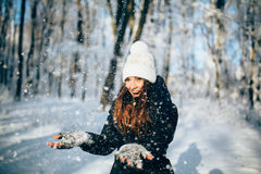 Girl  outdors in the forest and catch snowflakes. Girl Wearing Warm Winter Clothes And Hat Blowing Snow outdors in the forest and catch snowflakes Royalty Free Stock Images