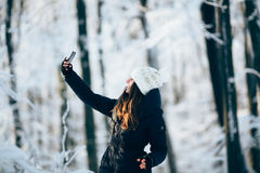 Girl outdors in the forest taking photo with phone (selfie). Girl Wearing Warm Winter Clothes And Hat  outdors in the forest taking photo with phone (selfie Royalty Free Stock Photo