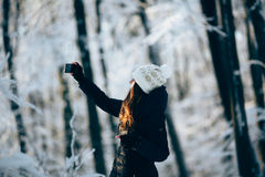 Girl outdors in the forest taking photo with phone (selfie). Girl Wearing Warm Winter Clothes And Hat  outdors in the forest taking photo with phone (selfie Stock Photo