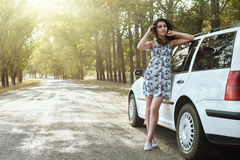Girl outside car on country road, bright sunlight and trees, summer season Stock Images