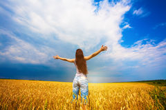Girl with outstretched arms is enjoys summer day Stock Images