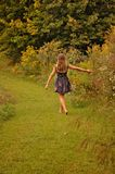 Girl walking alongside wild meadow flowers. Girl with outstretched hand walking in path alongside yellow goldenrod flowers in the late summer royalty free stock photo