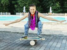 Girl on oval wooden deck for balance board. Plastic roller for balance board. Rocker-roller boards Stock Image