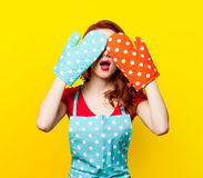 Girl with oven gloves and apron Stock Images