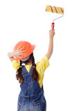 Girl in overall with paintroller. Girl in overall and hard hat with paintroller on the white wall, isolated on white Royalty Free Stock Image