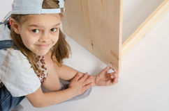 Girl in overalls collector furniture screw spins Royalty Free Stock Images