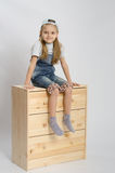 Girl in overalls collector relies on the chest shows class Royalty Free Stock Photos