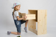 Girl in overalls furniture assembler inserts a drawer chest of drawers Royalty Free Stock Photo