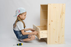 Girl in overalls furniture collector tries to insert drawer a chest of drawers Royalty Free Stock Photos