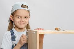Girl in overalls furniture collector tries to tighten the screw Royalty Free Stock Photos